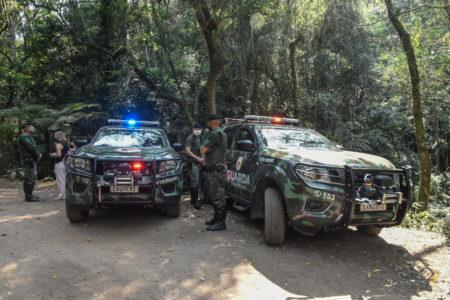 Veículos da Guarda Municipal estacionados em uma das vias da Serra do Japi com guardas fazendo a fiscalização da área conversando com as pessoas que circulam pelo espaço