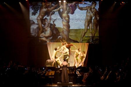 Palco de teatro, com iluminação sobre músicos e atores encenando, com painel luminoso ao fundo