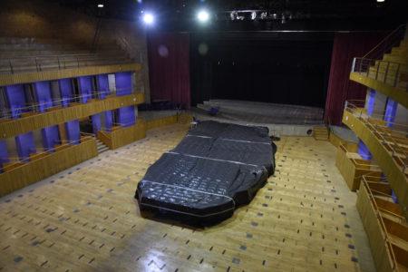 Teatro sem cadeiras e palco ao fundo com cortinas abertas