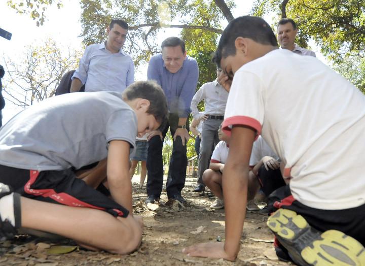 Prefeito observa crianças brincando no bosque da escola