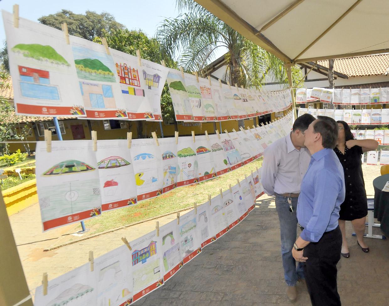 Prefeito observa desenhos dos alunos do bairro mostrando os locais que mais gostam na cidade