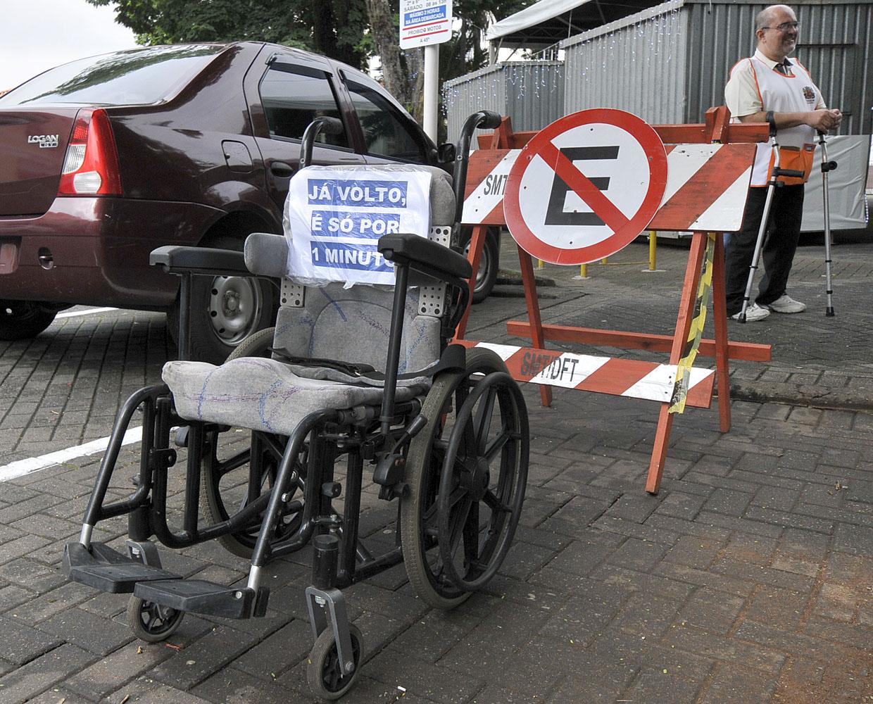 """Cadeira de rodas """"estacionada"""" em vaga comum é o símbolo da ação"""
