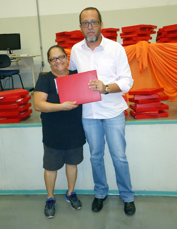 Diretor do CMEJA, José Ronaldo, entrega material para estudante