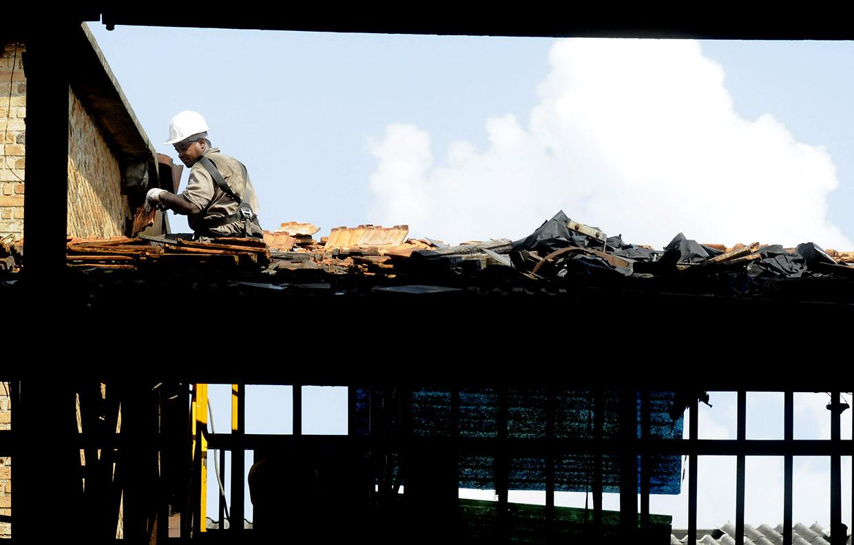 Operário especializado trabalha na retirada de telhas francesas