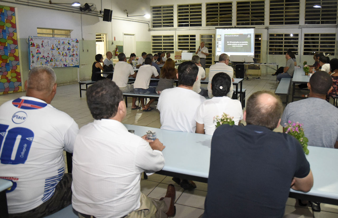 Pessoas assistem, no pátio da escola, apresentação sobre o Plano Diretor Municipal