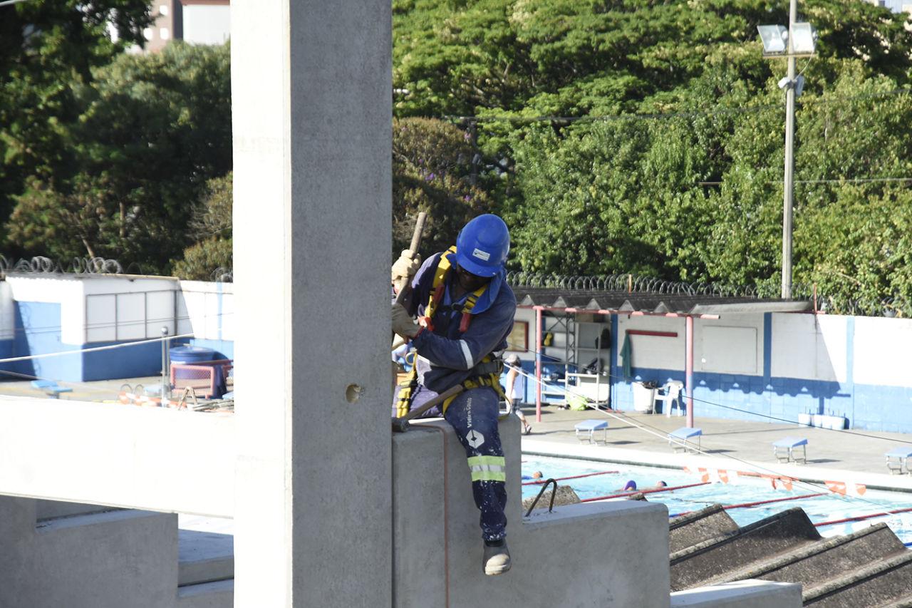Homem trabalhando na obra da arquibancada