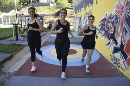 Três mulheres correndo em direção à câmera