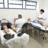 Atletas passam por avaliação, deitados em macas