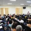 Palestrante fala para plateia lotada, em sala