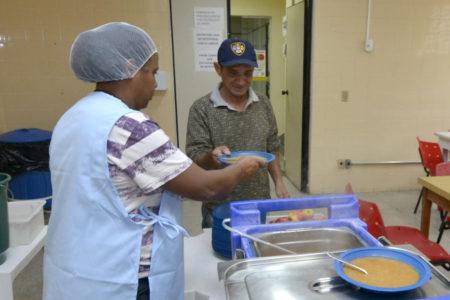 Auxiliar de cozinha entrega refeição