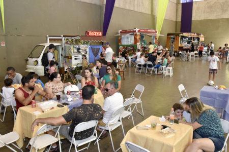 Pessoas lanchando em mesas com barracas de alimentação ao fundo