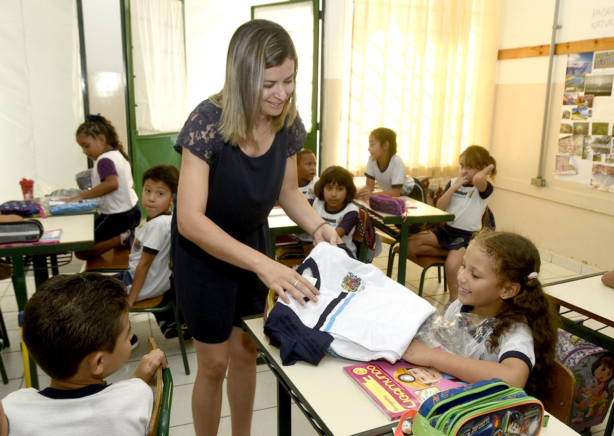 Criança recebe uniforme das mãos de uma professora