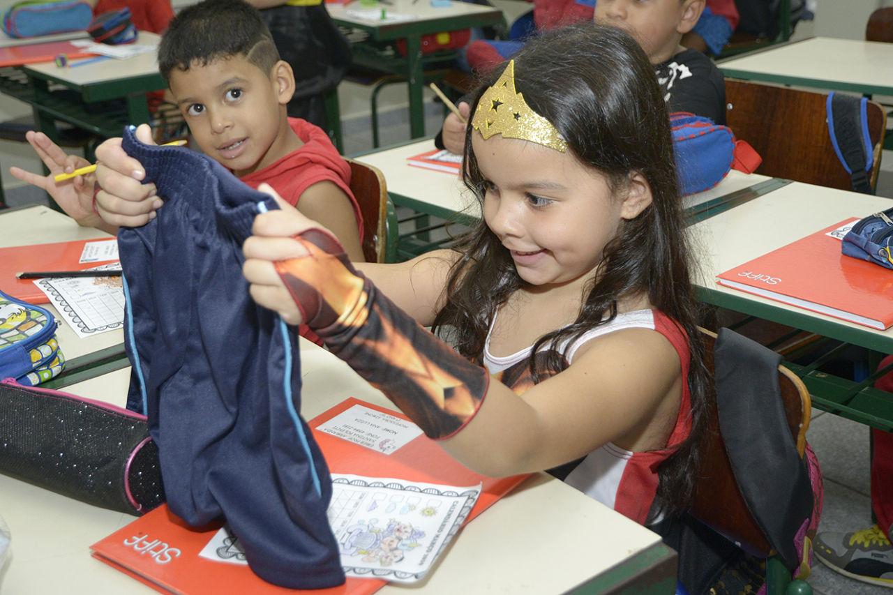 Aluna segura o uniforme em sala de aula
