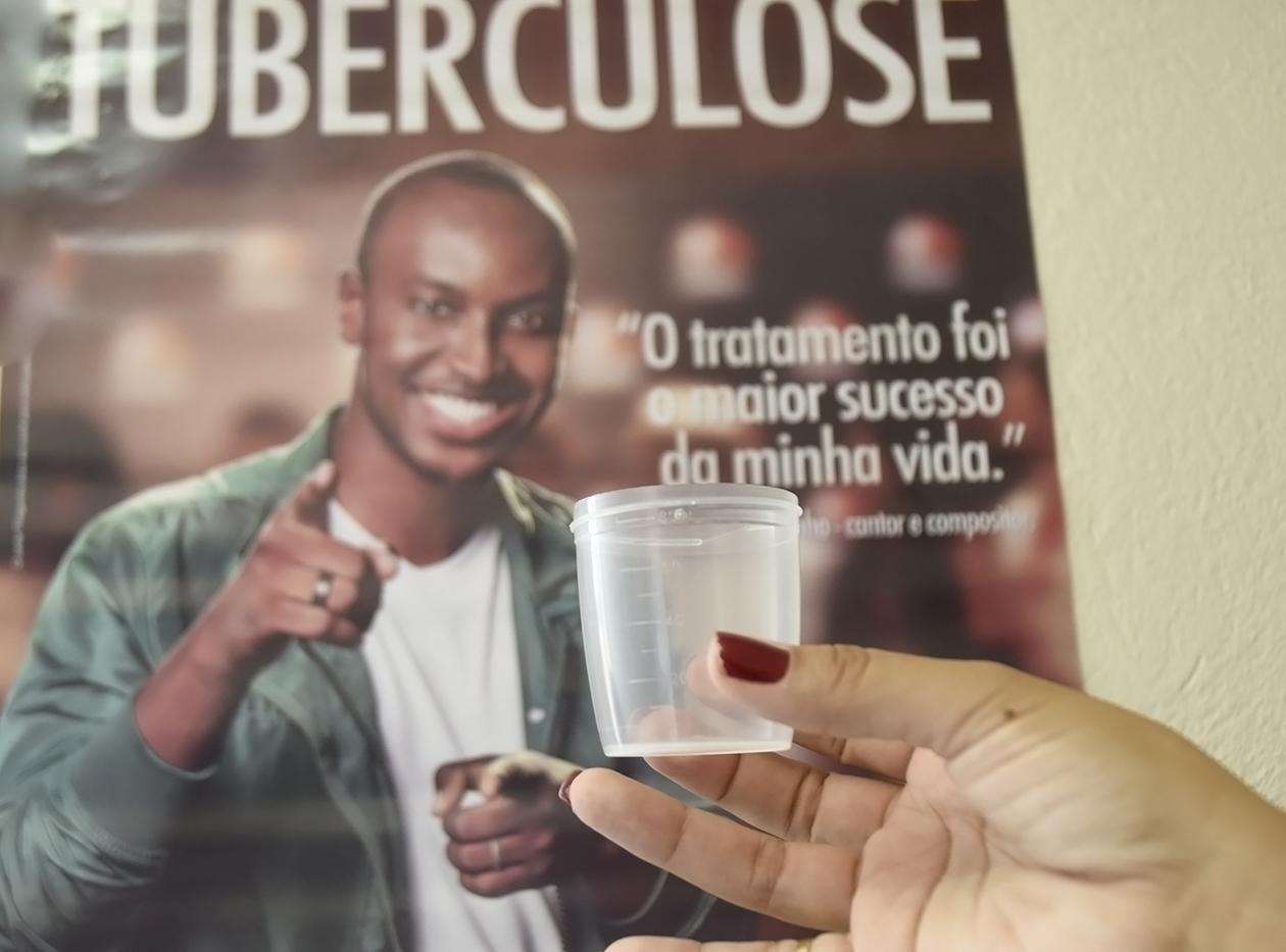 Mão segurando um copo de coelta e, ao fundo, cartaz da campanha