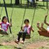 Três meninas brincando no balanço no parque