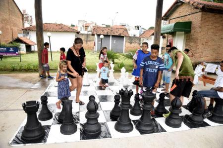 Crianças e pais brincam em xadrez gigante