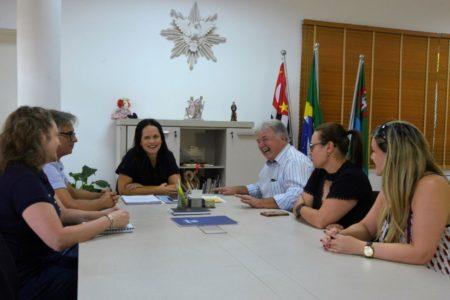 Primeira-dama fala durante reunião, com todos os participantes sentados à mesa