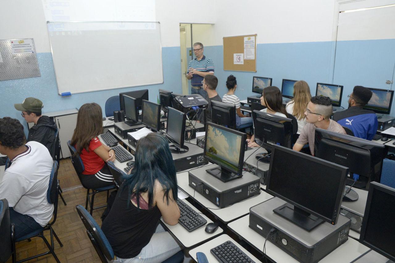 Alunos durante curso, sentados em frente aos computadores