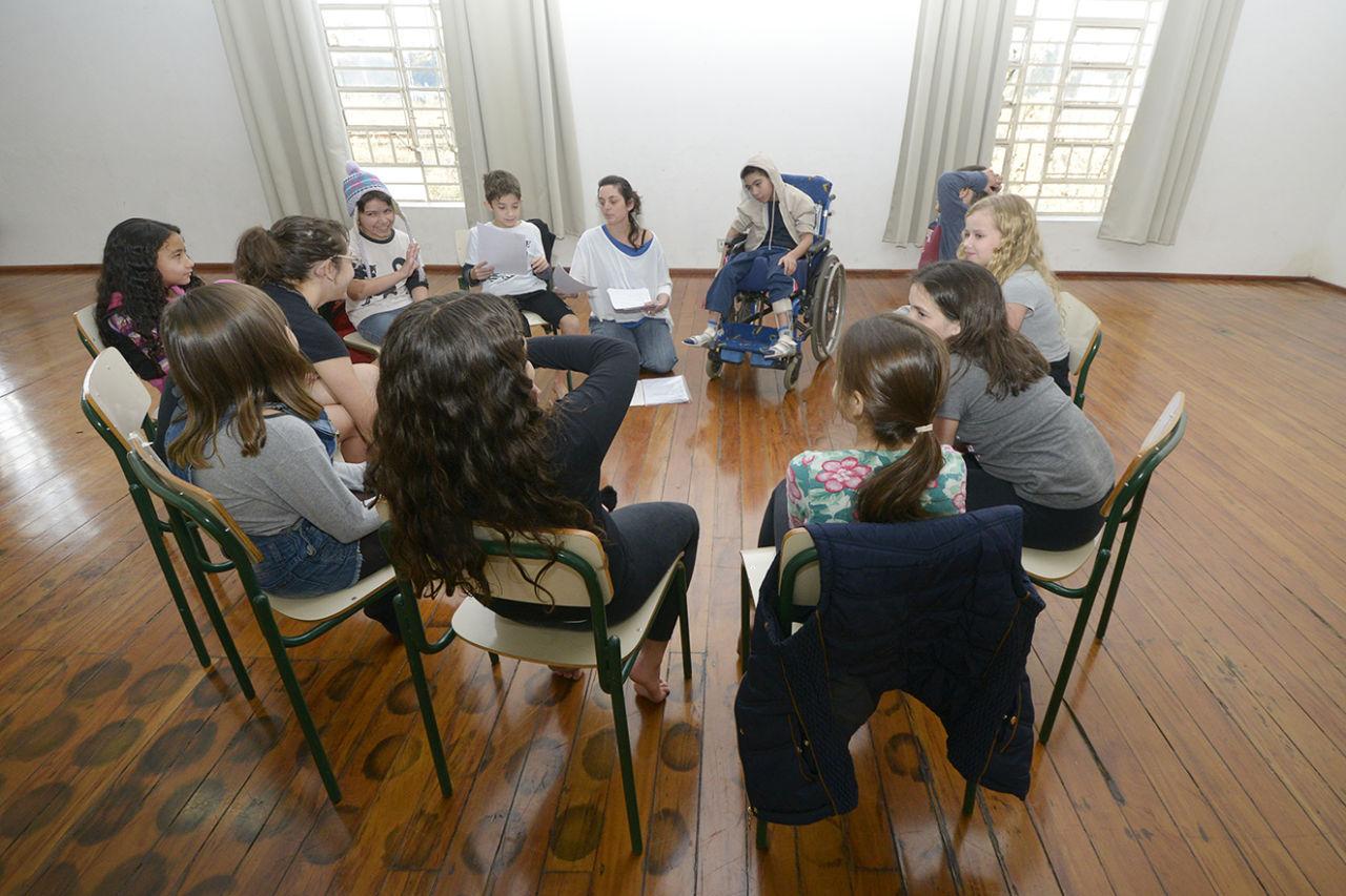 Crianças sentadas em círculo durante uma oficina na Sala Hermeto Pascoal do Complexo Fepasa