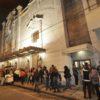 Fachada do Teatro Polytheama à noite, com público aguardando em fila