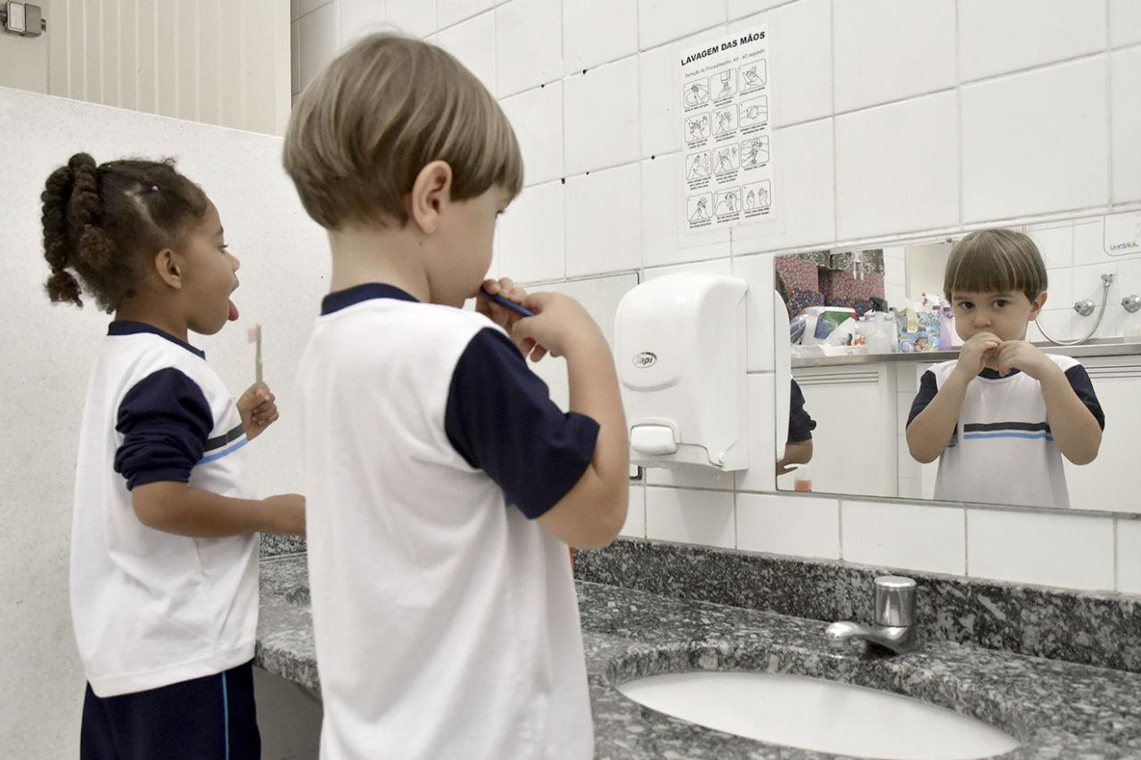Alunos estão em frente a espelho escovando os dentes