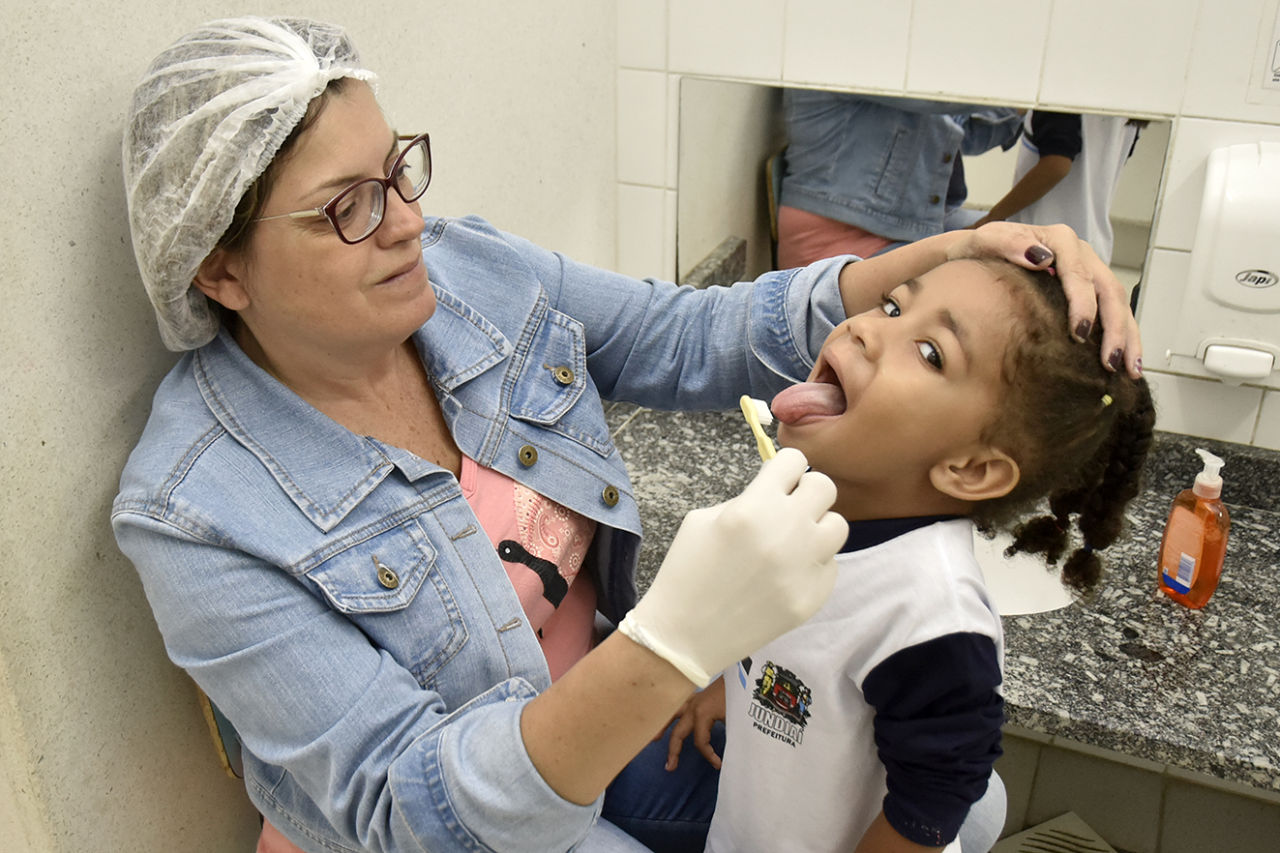 Mulher auxilia criança a escovar os dentes