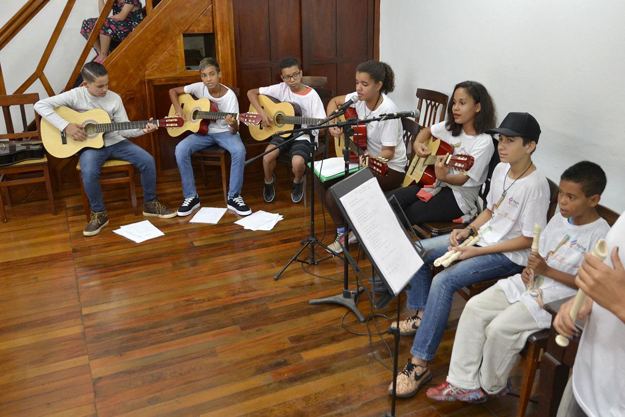 Crianças tocando violão em apresentação musical