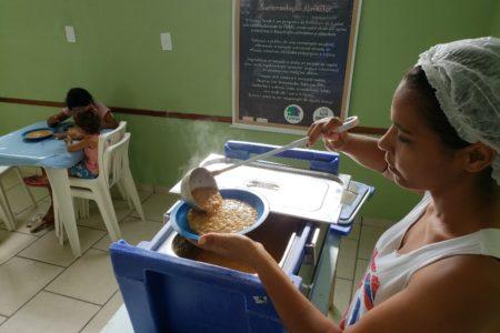 Funcionária serve refeição enquanto mulher e criança se servem