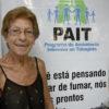 Paciente posa para foto em frente ao banner do programa