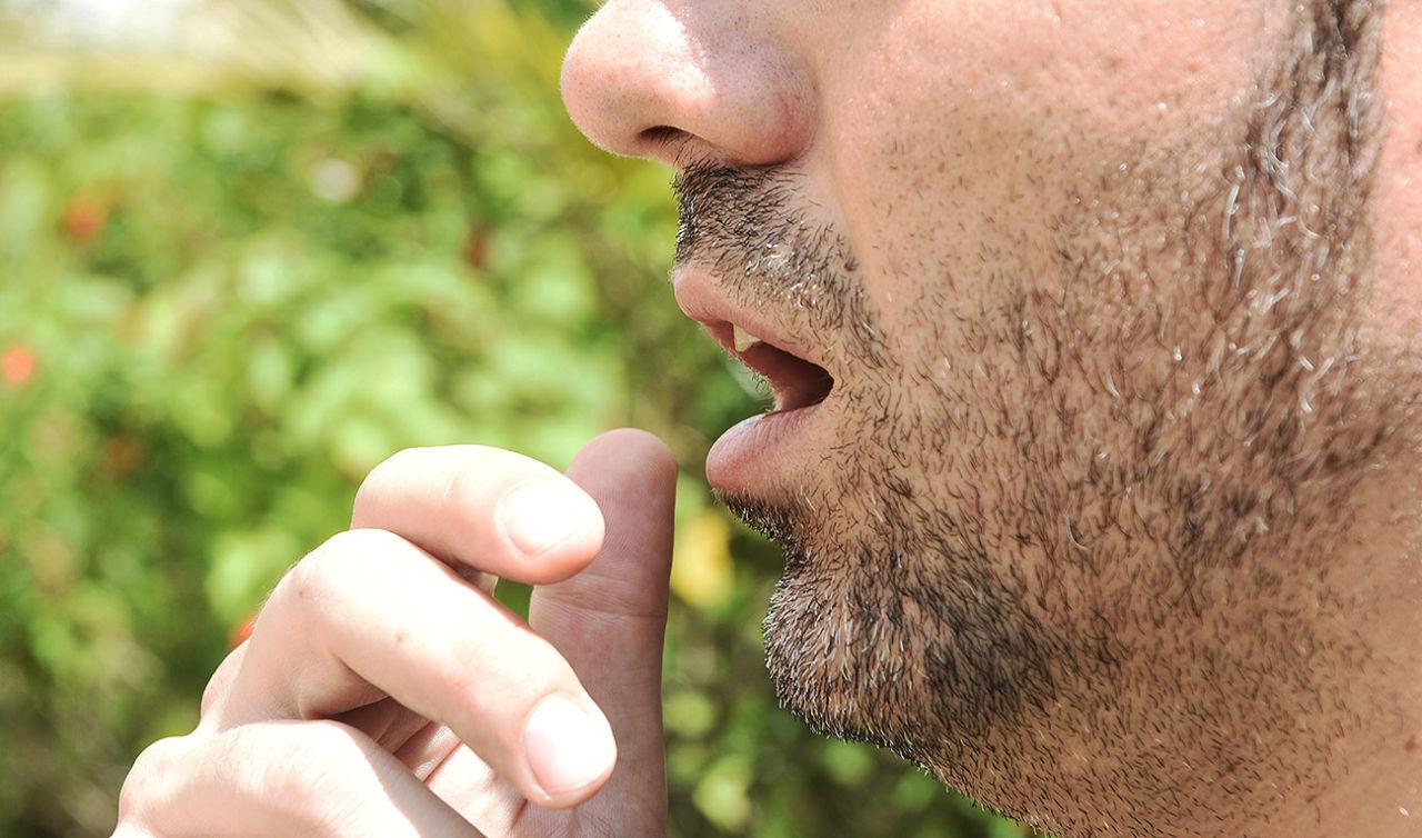 Homem levando a mão à boca para tossir