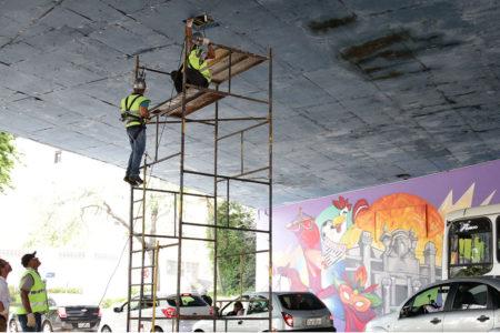Homens, em andaimes, fazem vistoria na parte de baixo de viaduto
