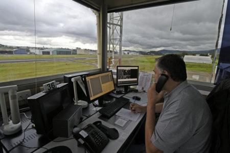 Técnico em atendimento na torre de controle do aeroporto com visão da pista e equipamentos de monitoramento de aviões