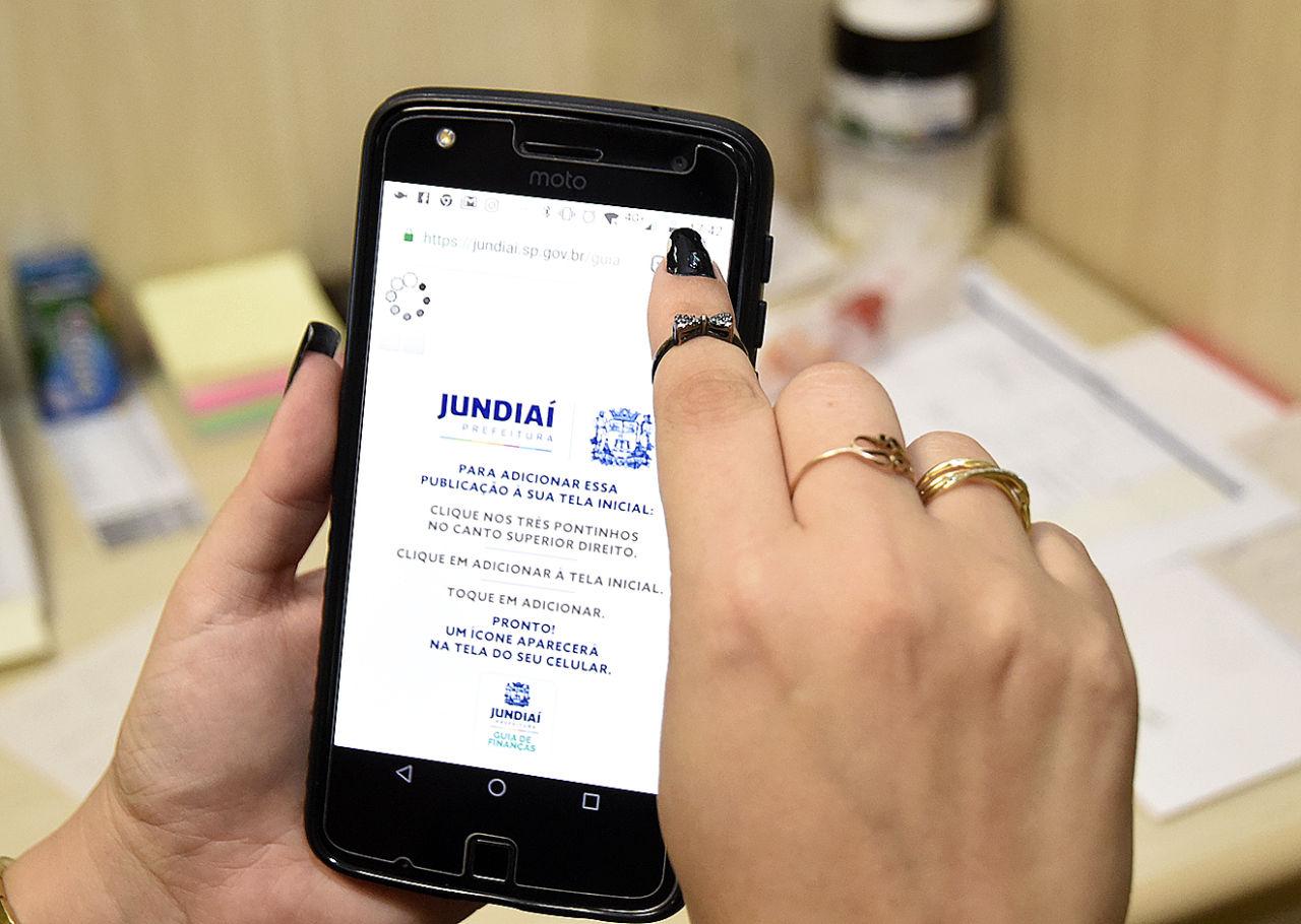 Mãos segurando celular com a tela de visualização do aplicativo
