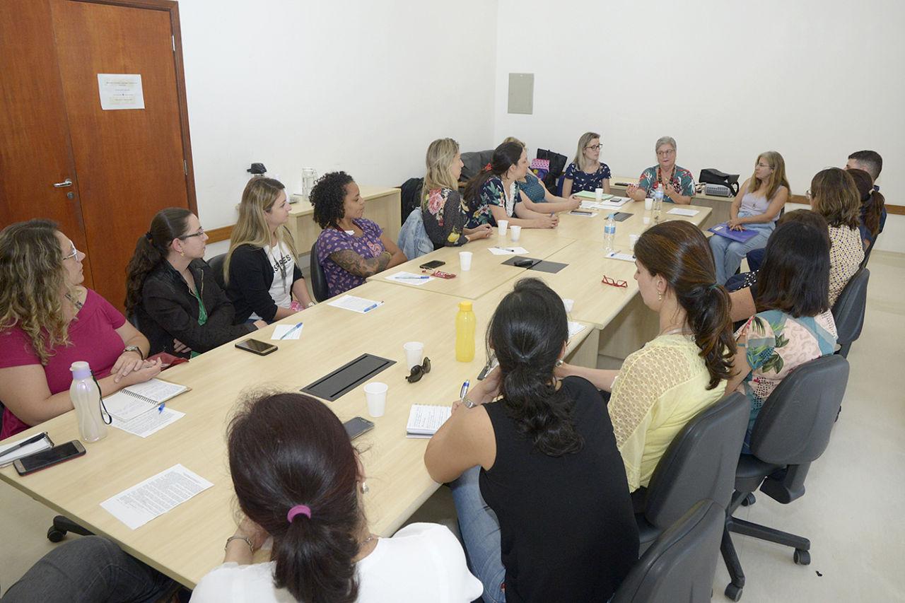 Pessoas sentadas ao redor de mesa de reunião