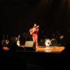 Cantor durante show, com violão na mão, outros instrumentos no palco e luz focada