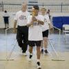 Atleta segura a pira olímpica, seguido de outros dois, todos com a camiseta da competição