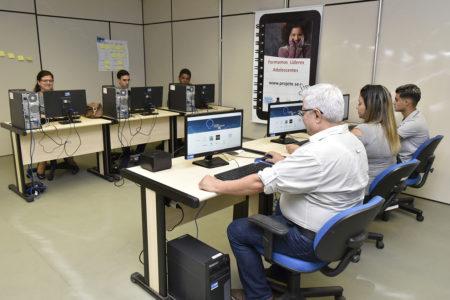 Seis pessoas usando computador, em duas fileiras, uma de frente com a outra