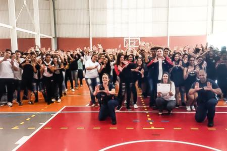 Foto dos agentes em ginásio, olhando para câmera e fazendo sinal com a mão