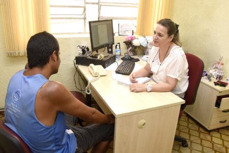 Atendimento a pessoa em situação de rua, não identificada, por profissional do Centro Pop, em mesa com computador