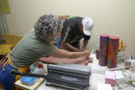 Oficineira dá instruções a aluno do Centro Pop durante oficina de artesanato