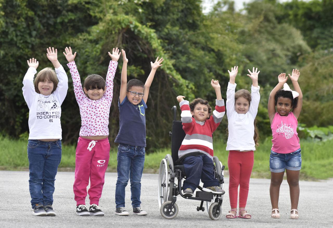 Crianças com as mãos levantadas, alinhadas