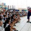 Crianças sentadas assistem PM colocando capacete em outro aluno