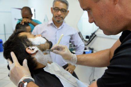 Homem tem a barba com espuma e sendo cortada por aulo, acompanhado pelo professor