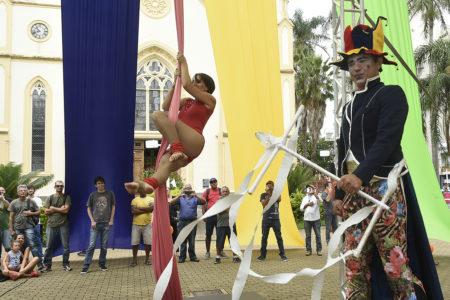 Apresentação de palhaço e acrobacia com pano em frente à catedral