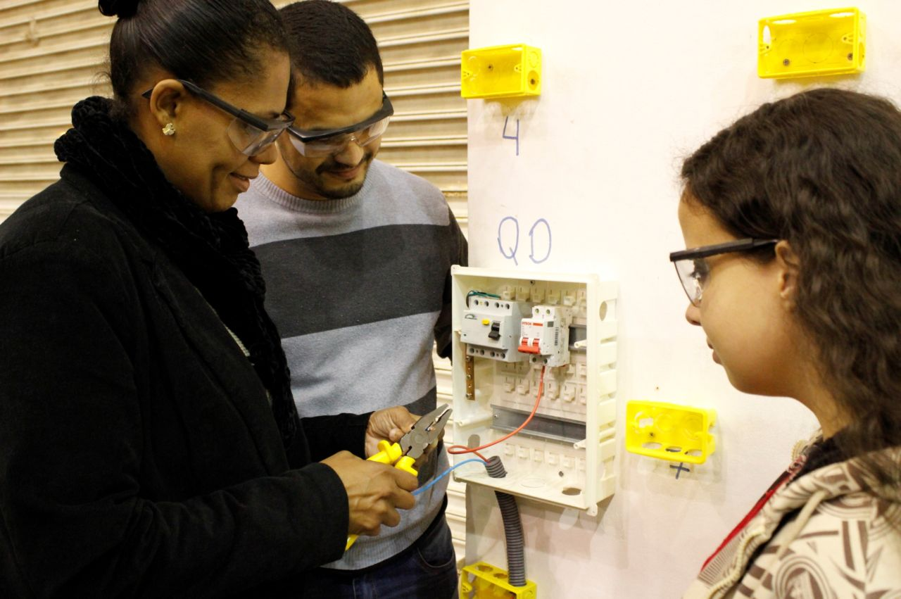 Alunos olham instalação elétrica durante curso