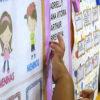 Mão de criança apontando para nome em mural