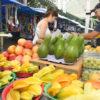 Mulher em banca de feira com frutas expostas