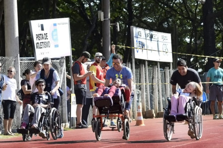 Três pessoas empurrar três cadeirantes na pista de atletismo do Bolão