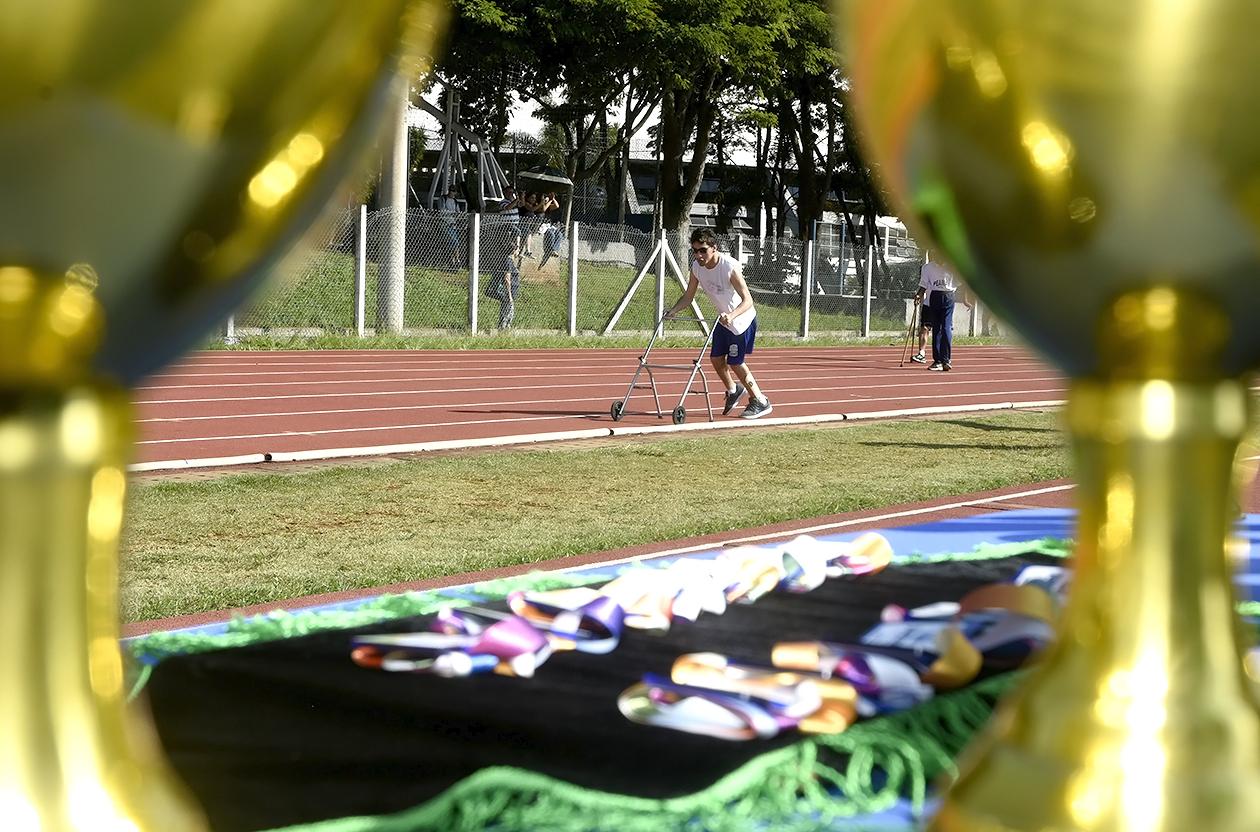 Foto feita entre medalhas com foco em atleta na pista de atletismo