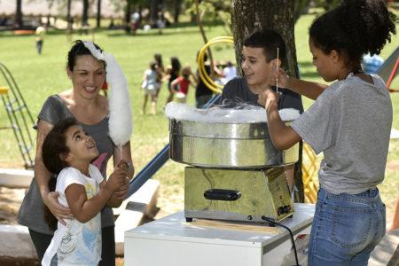 Criança olha com felicidade para um algodão doce, em frente a uma máquina que produz a sobremesa